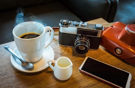 Vintage camera with coffee cup