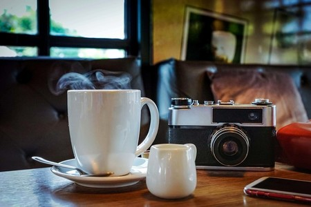 Vintage camera with coffee cup  glasses and smartphone on the ta