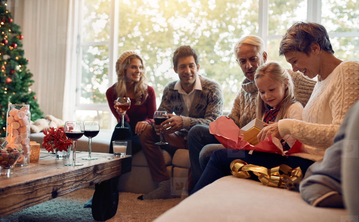 Cute girl with family and opening christmas present