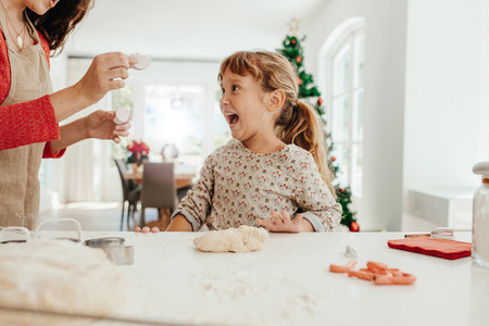Mother and daughter in kitchen making cookies for Christmas
