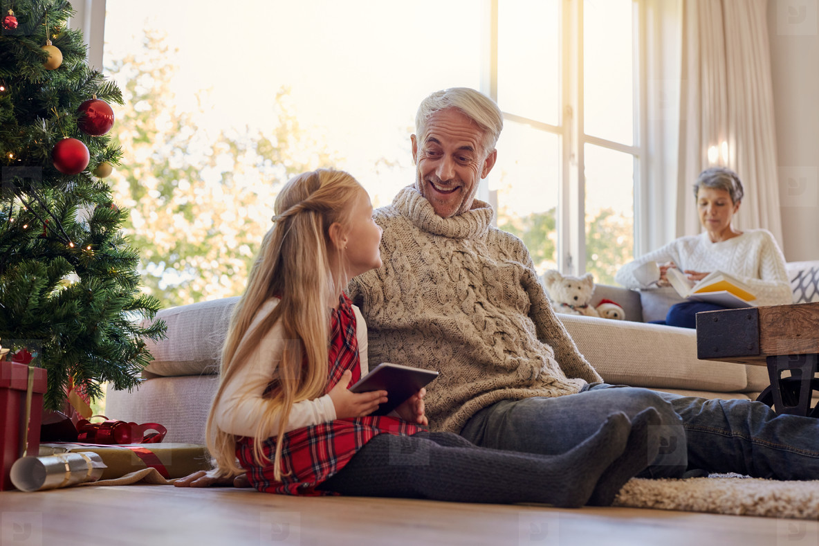 Senior man and granddaughter with digital tablet at home