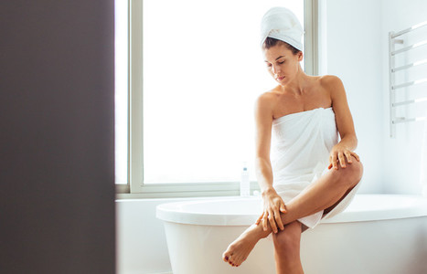 Woman taking care of her body after bath