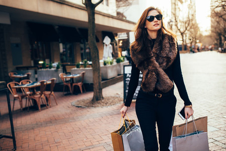 Woman outdoors on road carrying shopping bags