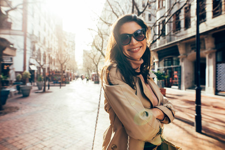 Stylish female model with sunglasses on city street