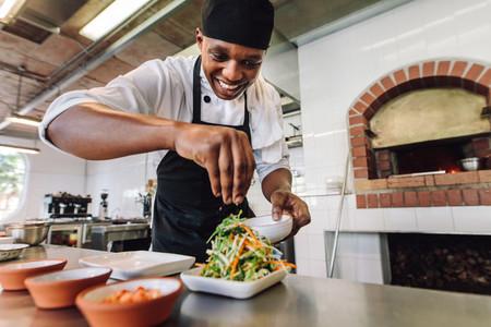Male chef preparing salad in kitchen