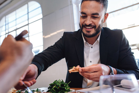 Young businessman having food in restaurant