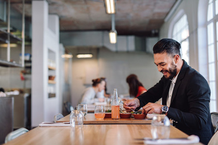 Happy businessman having food in restaurant