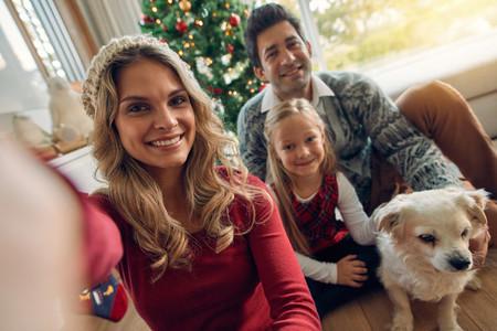 Caucasian family taking photos at Christmas
