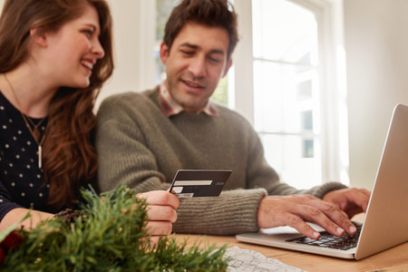 Couple shopping online at home for Christmas