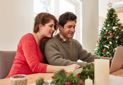 Young couple at home shopping online for christmas