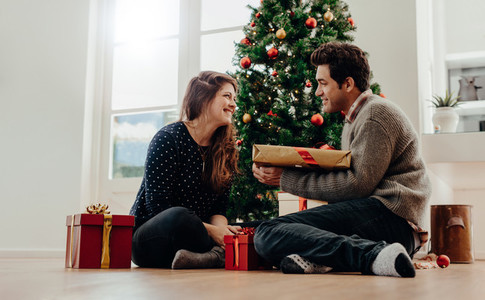 Young couple exchanging Christmas gifts sitting beside a Christm
