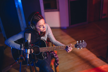 Woman playing guitar in a recording studio