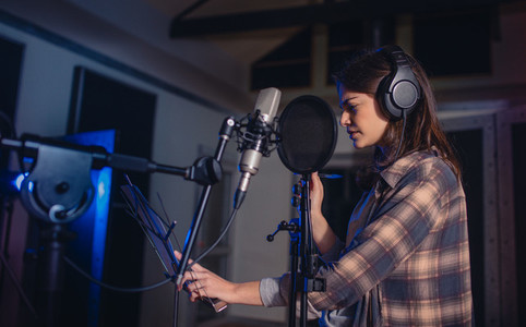 Woman recording music in studio