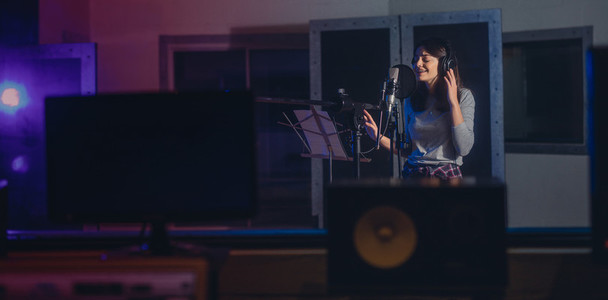 Woman recording a song in music studio