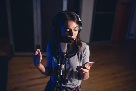 Singer recording song for her album in studio