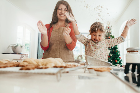 Mother and daughter having fun while making Christmas cookies