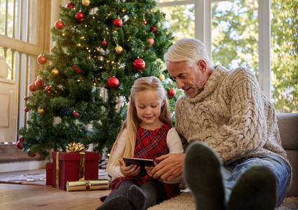 Senior man with granddaughter using digital tablet during christ