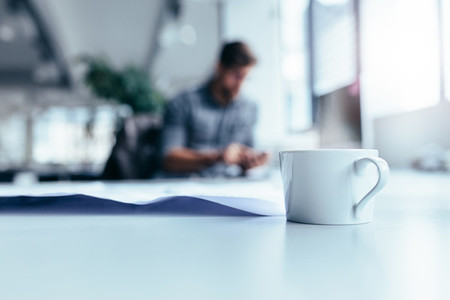 Cup of coffee on desk with man working in background