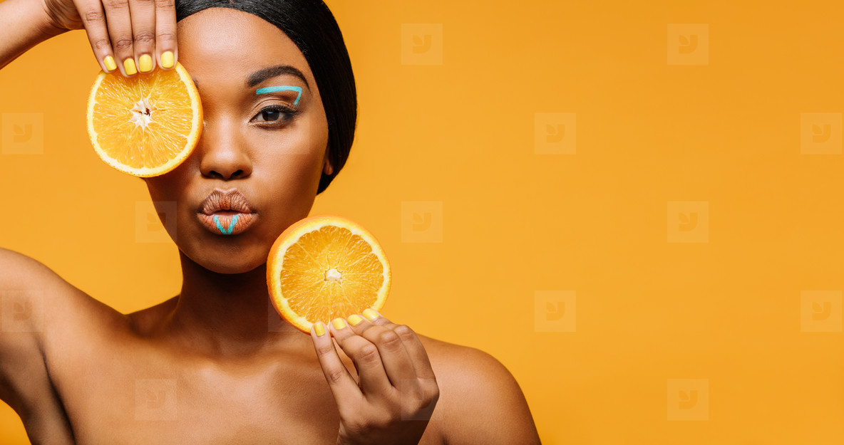 Woman with artistic makeup and orange in hand