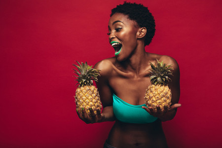 Black woman with pineapples in hand