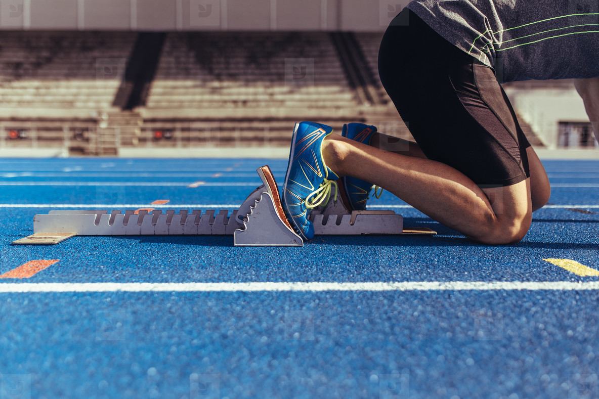 Sprinter resting his feet on starting block on running track