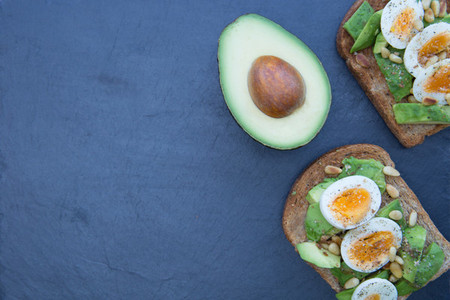 Avocado eggs on dark background with copy space