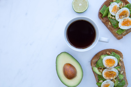 Breakfast of avocado and eggs on brown toast