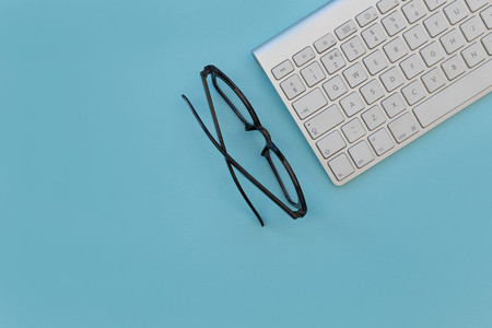 Eyeglasses and computer keyboard with copy space on bright blue