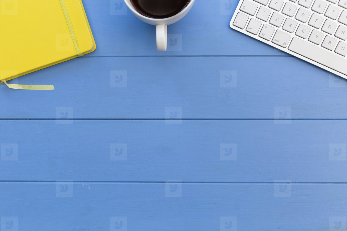 Computer keyboard  coffee cup and notebook on blue wood desk