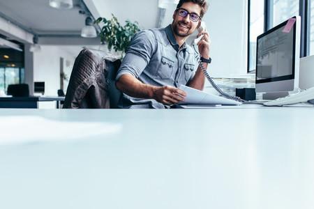 Businessman talking on landline phone