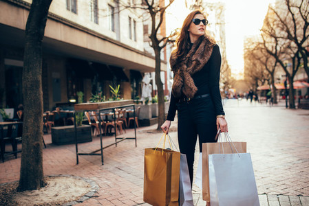 Stylish woman standing on the street with shopping bags