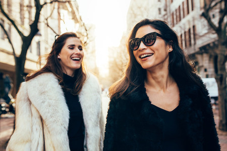 Female friends in warm clothes walking on the city street