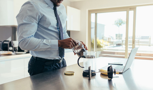 Businessman preparing coffee at home