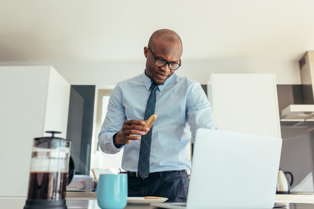 Businessman working on laptop computer while eating breakfast