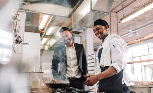 Restaurant manager with chef cooking in kitchen