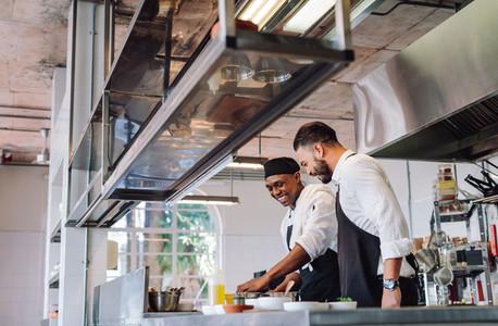 Two cooks preparing food in restaurant kitchen