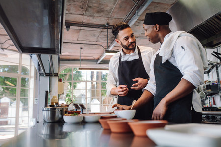 Chefs talking while cooking food in commercial kitchen
