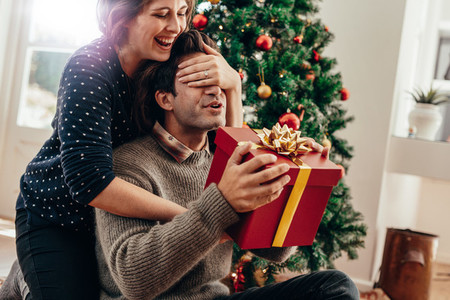 Young couple having fun celebrating Christmas with gifts