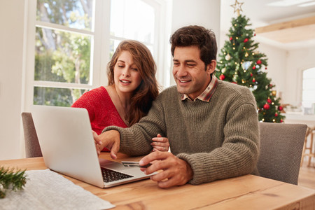 Happy young couple shopping online for christmas