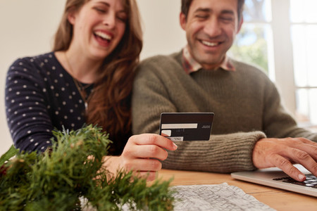 Young couple shopping online for christmas