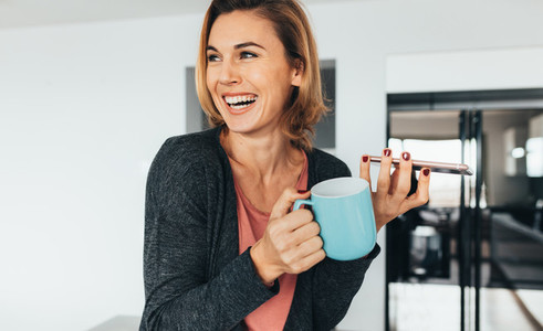 Woman holding mobile phone and coffee mug