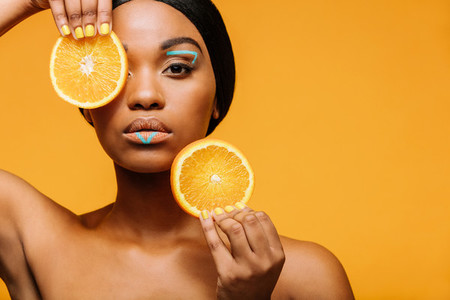 Woman with vivid makeup and orange slices