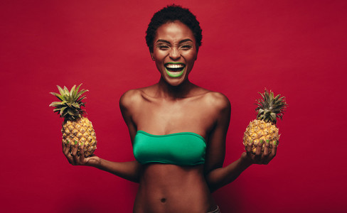 Laughing african woman with pineapples