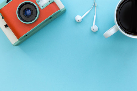 Camera earphones and coffee cup on bright blue background