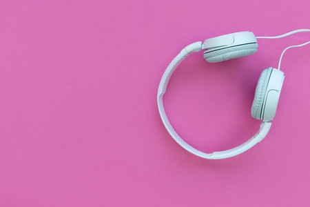 White music headphones on bright pink background