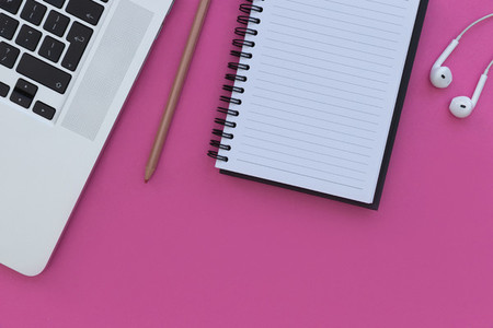 Notebook laptop computer and earphones on bright pink background