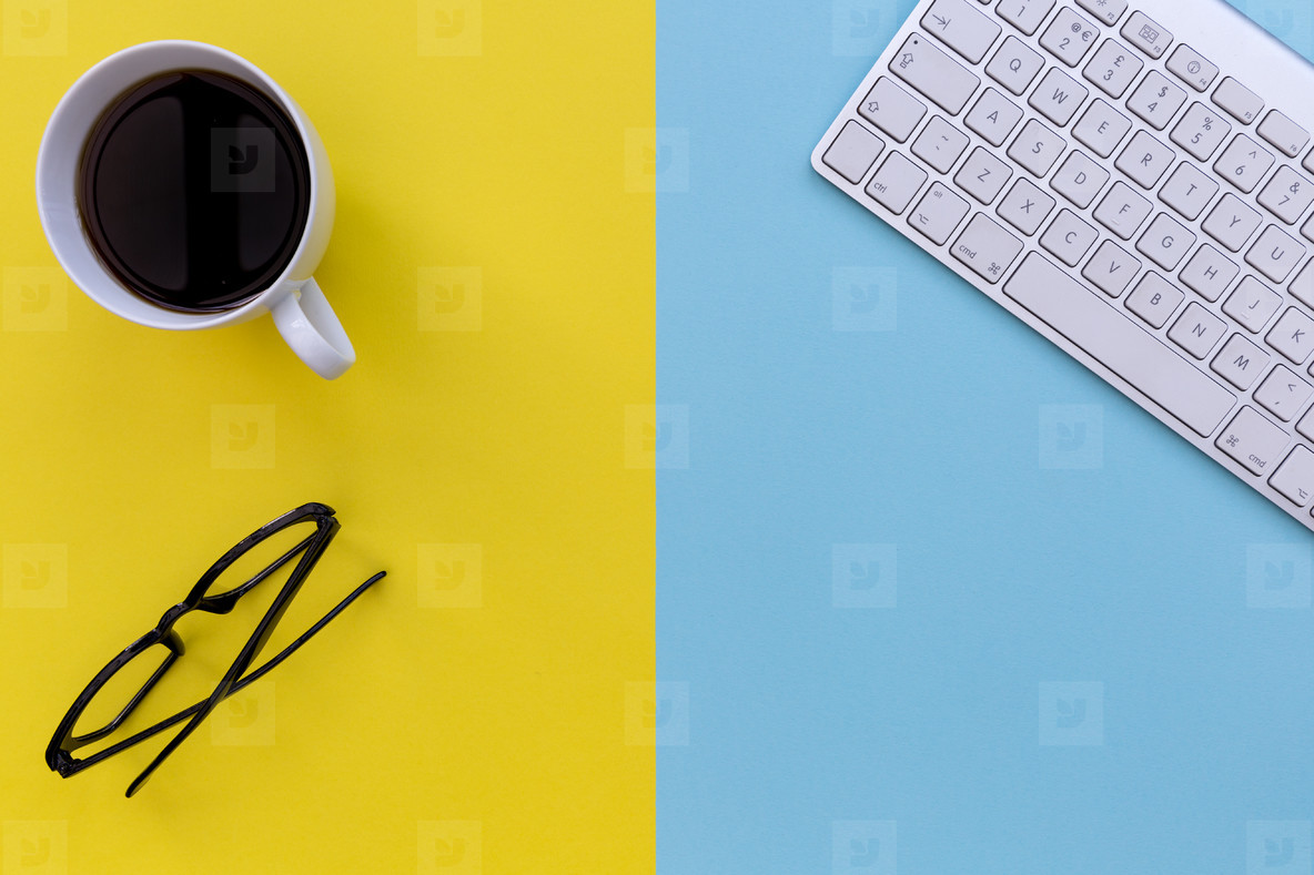 Computer keyboard eyeglasses   coffee on bright yellow and blue