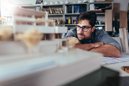 Architect in office looking at house model