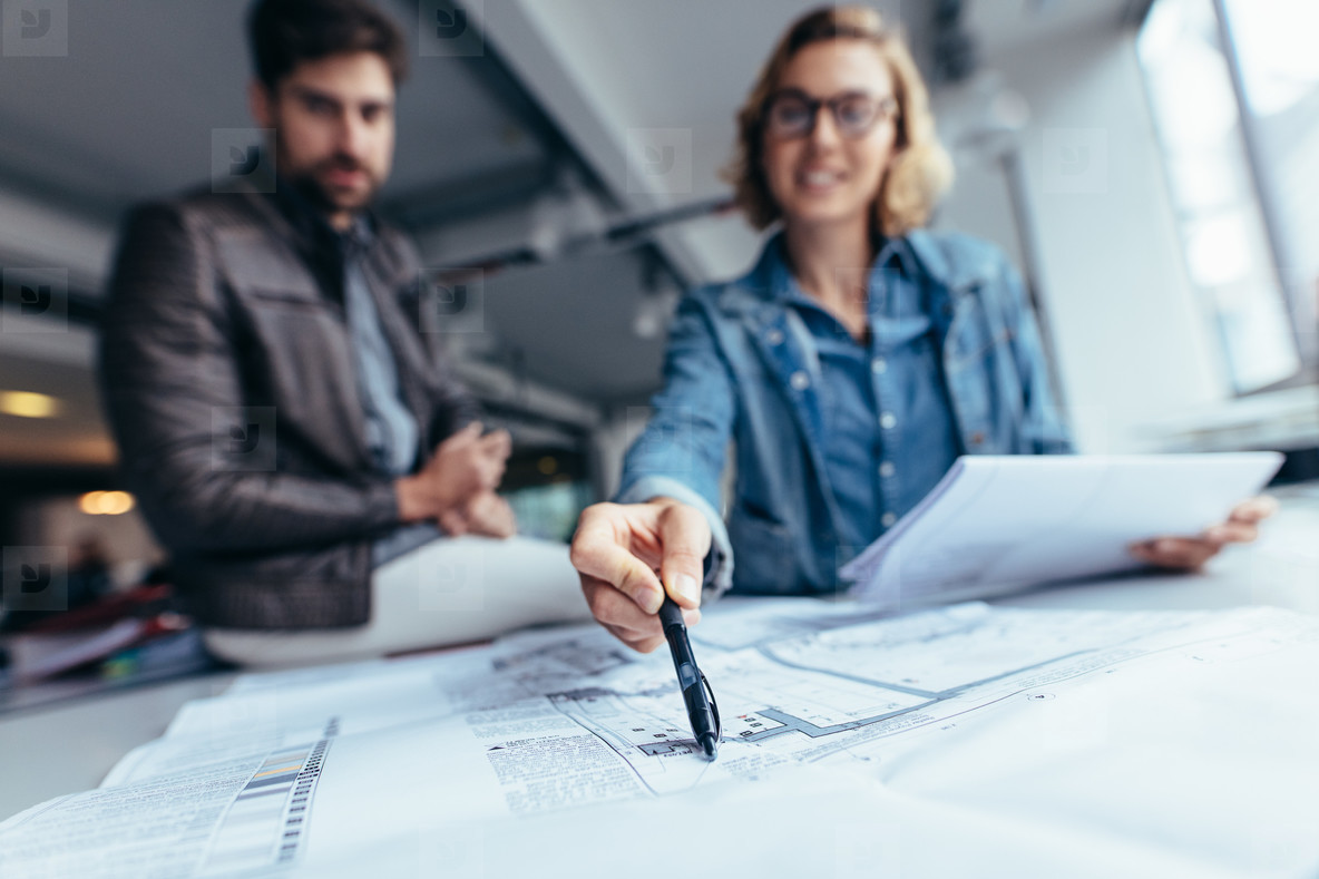 Designers working on blueprint in office