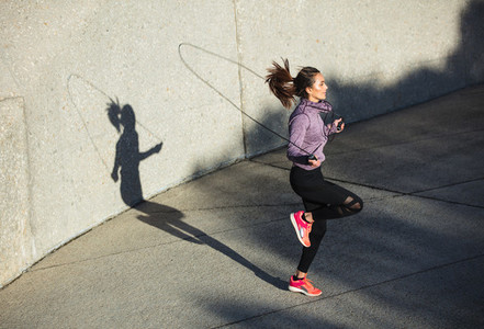 Healthy woman skipping ropes outdoors